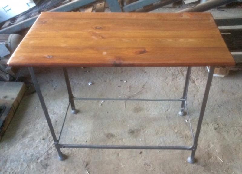 Mesa con tablero de madera y patas de forja antigua con remaches. Mide 50 cm x 94 cm x 75 cm de alto