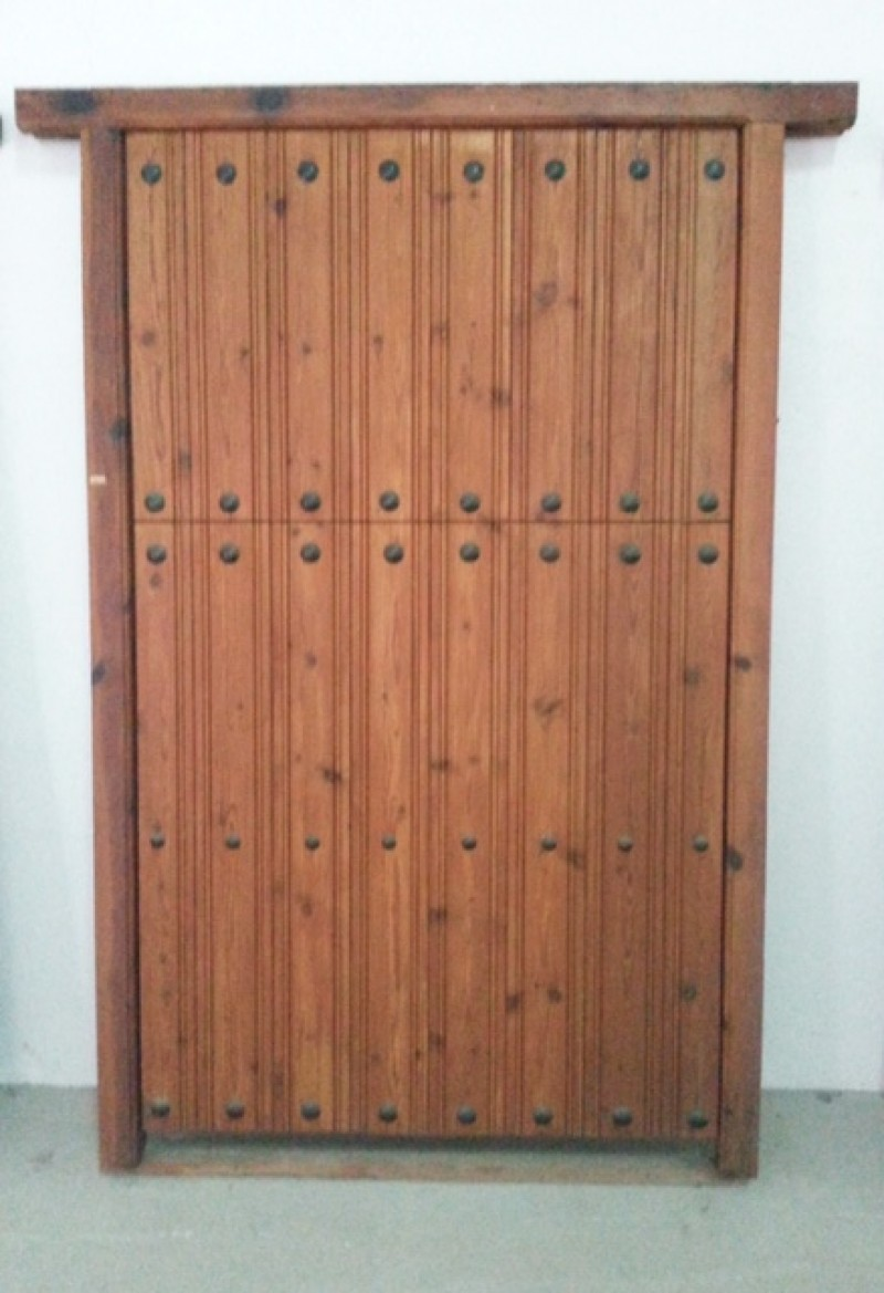 Puerta de madera partida, apertura a izquierdas, sin cerradura, con bisagras de seguridad. Mide 2.06 cm de alta x 1.33 cm de ancha.