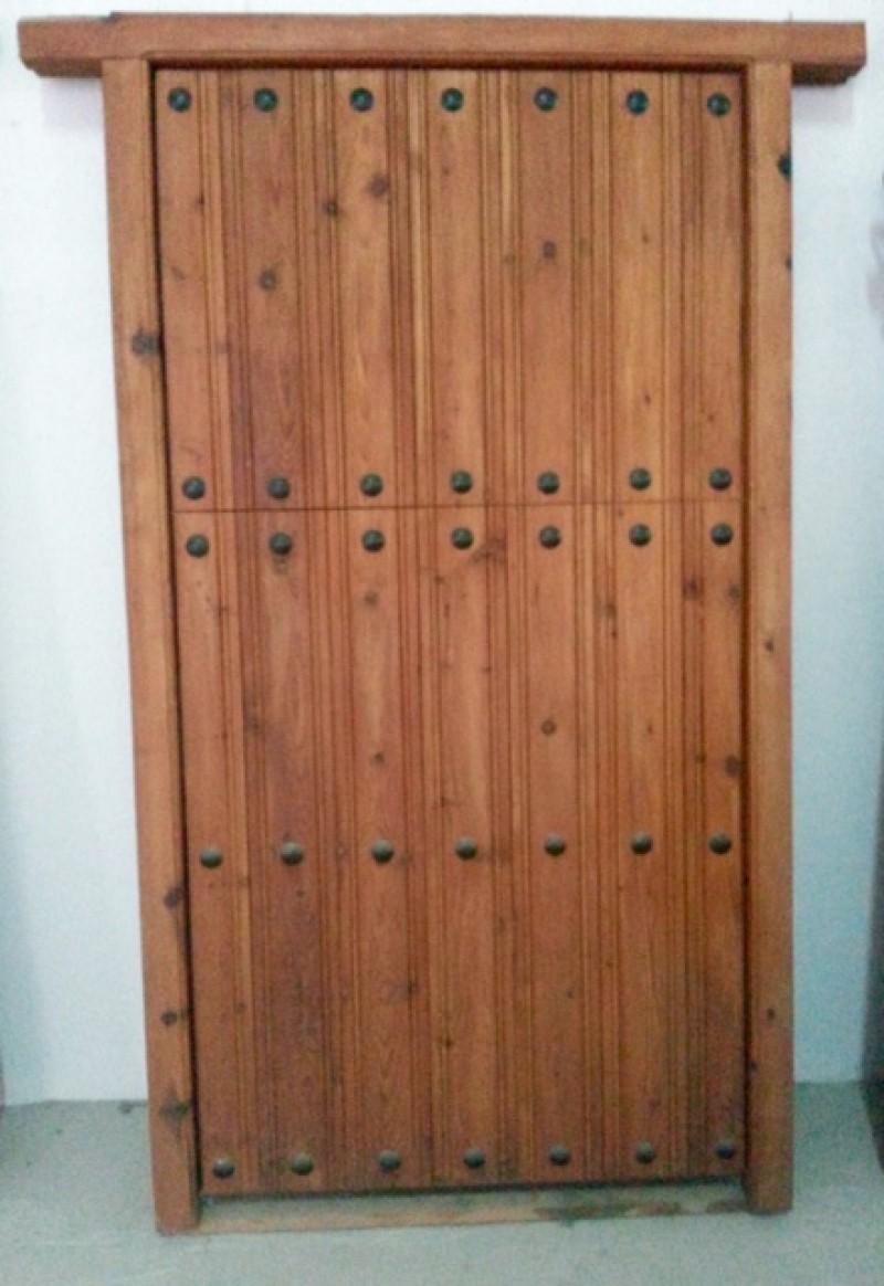 Puerta de madera partida, apertura a izquierdas, sin cerradura, con bisagras de seguridad. Mide 2.06 cm de alta x 1.16 cm de ancha.