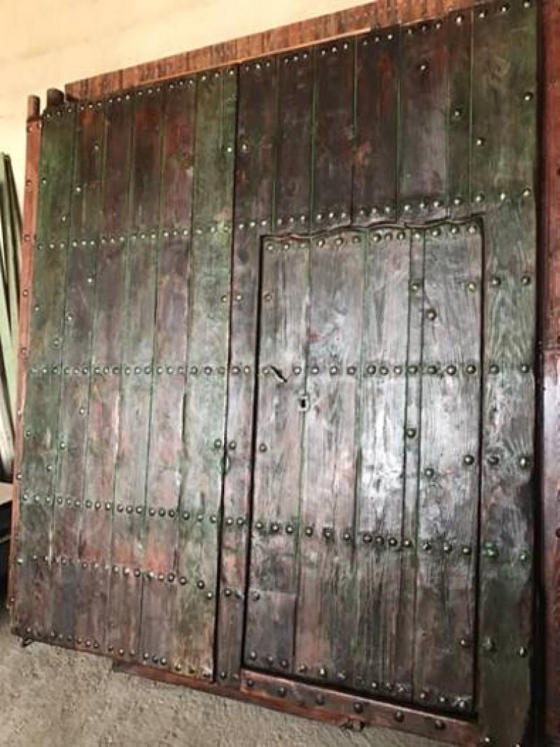 Puerta de madera antigua restaurada. Mide 2,23 cm de ancho x 2.50 cm de alto, y tiene una puerta de paso que mide 83 cm x 1.65 cm.