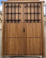 Puerta de madera de pino en dos hojas con dos ventanos y rejal. Mide 1.60 cm de ancho x 2.10 cm de alto