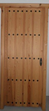 Puerta de madera de pino. Tabla clareada y clavos. Mide: 94 x 2,10 cm