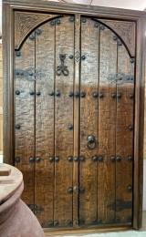 Puerta de exterior de dos hojas, madera maciza de pino rojo, tallada. Mide 1.44 cm x 2.24 cm de alta
