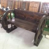 Banco de madera hecho con dos ruedas de carro romanas. Mide 1,45 cm de largo x 95 cm de fondo x 95 cm de alto.