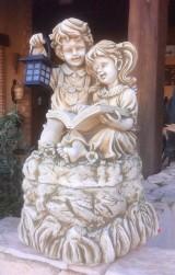 Figura de niños leyendo con farolillo de luz solar, piedra artificial color ocre. Mide 38 cm x 38 cm x 68 cm de altura