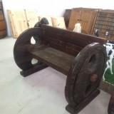 Banco de madera hecho con dos ruedas de carro romanas. Mide 1,35 cm de largo x 90 cm de fondo x 94 cm de alto.