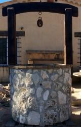 Pozo de piedra con arco de madera antigua. Piedra gris. Mide 1,30 cm x 2,10 cm alto.