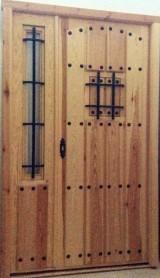 Puerta de madera de pino. Con fijo lateral con reja. Cerradura de seguridad de alto en bajo. Mide 1,30 x 2,10 cm.
