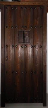 Puerta madera de pino pintada color nogal con chorreo de arena. Con ventano y reja. Mide 94 x 2,10 cm